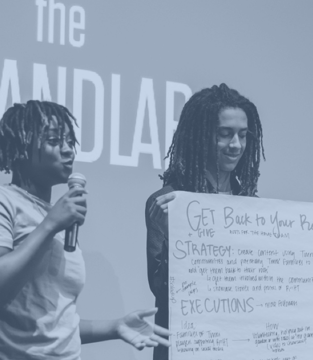 Two students holding up a poster for a project about strategy and execution.